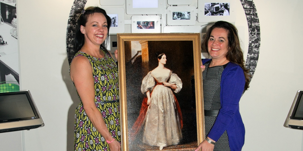 Extra Technology's Lisa Mannion and Judith Saffer, holding a portrait of Ada Lovelace, at The National Museum of Computing